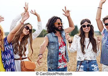 Amigos hippies felices bailando en el campo de cereal