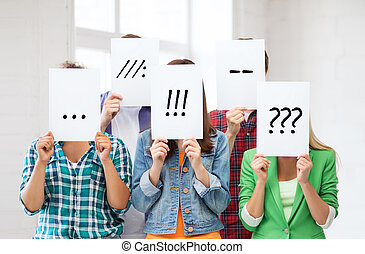 Amigos o estudiantes cubriendo caras con papeles