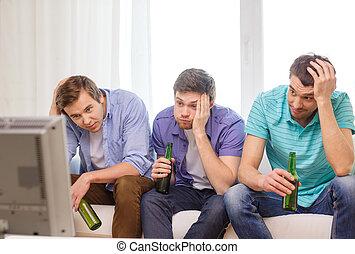 Amigos tristes con cerveza viendo deportes
