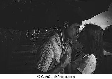 Amor bajo la lluvia Silueta de la pareja de besos bajo el paraguas