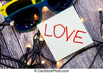 Amor escrito a mano en un papel blanco de color rojo. Dos gafas de sol en varias combinaciones de colores con luces puestas en el orden aleatorio con antecedentes de madera. Día de San Valentín o concepto de amor.