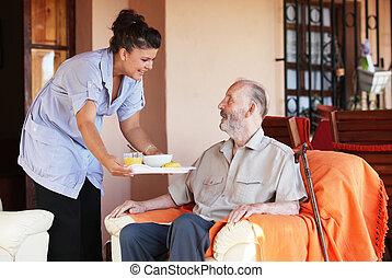 Anciano siendo traído comida por cuidador o enfermera
