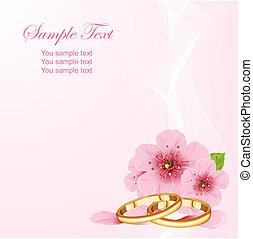 Anillos de boda y flor de cerezo