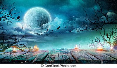 Antecedentes de Halloween, mesa vieja con velas y ramas en una noche espeluznante con luna llena