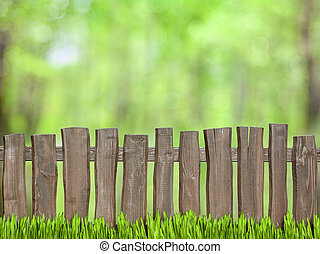 Antecedentes verdes con cerca de madera