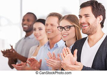 Aplaudiendo a las innovaciones corporativas. Un grupo de alegres empresarios aplaudiendo a alguien mientras están en fila