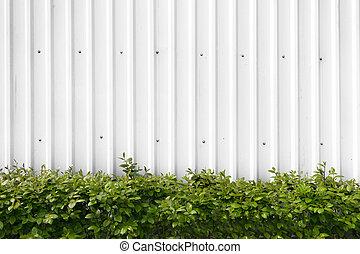 Arbustos con hojas verdes en una cerca de metal blanco
