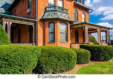 Arbustos frente a una vieja casa en Spring Grove, Pennsylvania.