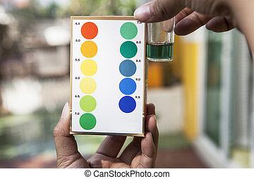 Archivo de mano sosteniendo pruebas de prueba de agua comparando el color