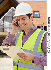 Arquitecto en el edificio usando teléfono móvil