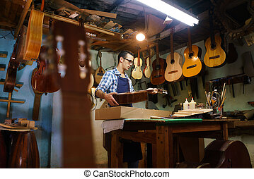 Artisan fabricante de laúd almacenando instrumentos de guitarra en caso de cliente