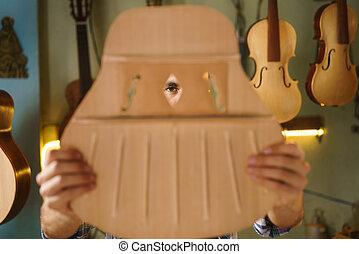Artisan fabricante de laúd cincelando la guitarra inspeccionando agujeros en la caja acústica