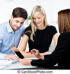 Asesor financiero explicando a la pareja mientras apunta a la tabla digital en la oficina