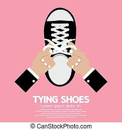 Atando zapatos.