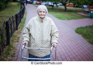 Atractiva anciana con Walker al aire libre