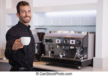 Atractivo camarero ofreciendo una taza de café a la cámara