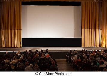 Audiencia frente a la pantalla de cine blanco