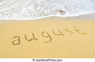 August - escrito en arena en la textura de playa
