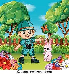 Aventura niño lindo con conejo en un jardín de flores