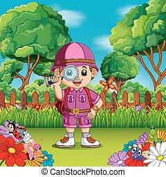 Aventura niño lindo sosteniendo una lupa en un jardín de flores