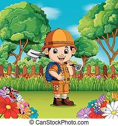 Aventura niño lindo sosteniendo una pala en un jardín de flores