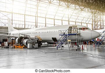 Aviones en el hangar en mantenimiento de placas, interiores, reparación de motores.