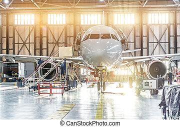 Aviones pasajeros en mantenimiento de reparación de motores en el hangar del aeropuerto.