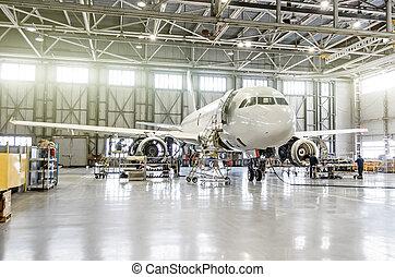 Aviones pasajeros en mantenimiento del motor y la reparación de fuselaje en el hangar del aeropuerto.
