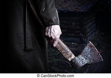 Axe con sangre en mano masculina