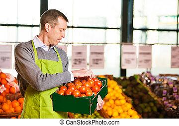 Ayudante de mercado con una caja de tomates