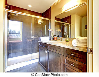 Baño con armario de madera y ducha de cristal.