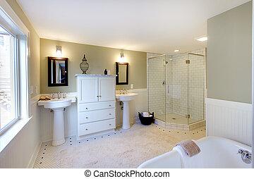 Baño de lujo con bañera de hierro y duchas y lavabos dobles.