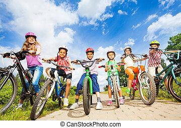 Bajo el ángulo de vista de los niños en cascos con bicicletas