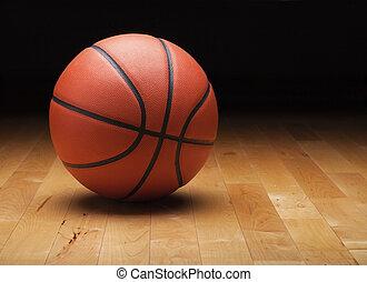 Baloncesto con un fondo oscuro en el suelo de un gimnasio de madera
