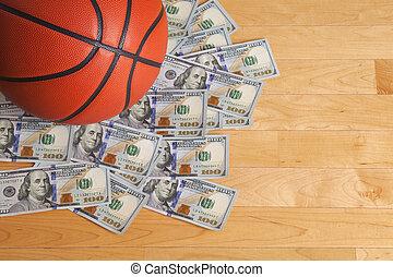 Baloncesto en pila de billetes de cien dólares