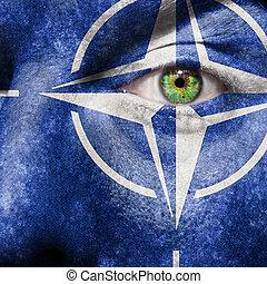 Bandera pintada en la cara con ojos verdes para mostrar apoyo a la OTAN