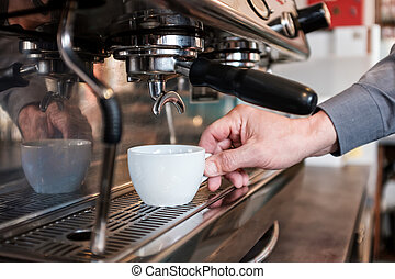 Barista poniendo taza en la máquina de café para hacer expreso fresco