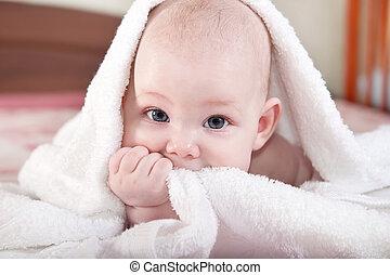 Bebé bajo toalla blanca
