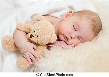 Bebé recién nacido durmiendo en la cama de piel