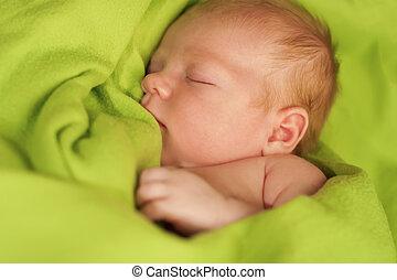 Bebé recién nacido durmiendo en una manta verde