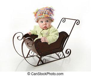 Bebé sentado en un trineo