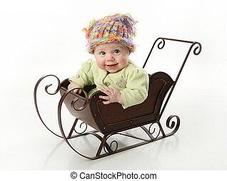 Bebé sonriente sentado en un trineo