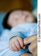 Bebé sosteniendo la mano de la madre