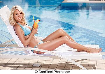 Belleza con cóctel. Mujeres atractivas en bikini en la silla de cubierta, junto a la piscina y sosteniendo un cóctel en su mano