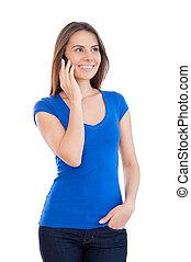Belleza en el teléfono. Una joven alegre hablando por teléfono y sonriendo mientras está aislada en blanco