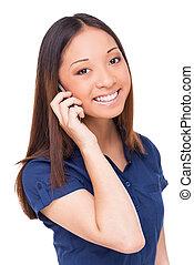 Belleza en el teléfono. Una joven asiática alegre hablando por el móvil y mirando a la cámara mientras estaba aislada en blanco