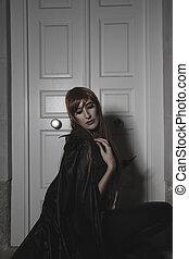 Belleza oscura bajo la lluvia, mujer pelirroja con abrigo largo y negro