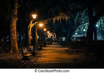 Benches y árboles con musgo español a lo largo de una pasarela por la noche, en Forsyth Park, en Savannah, Georgia.
