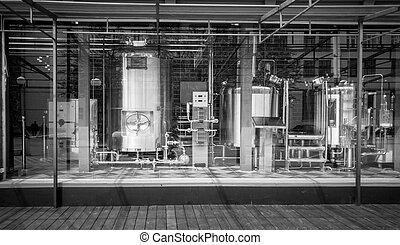 Blanco y negro con grandes cisternas y tuberías en la cervecería