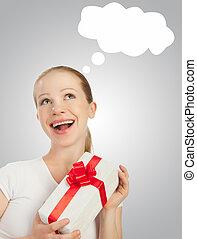 Bonita chica alegre con un regalo de Navidad